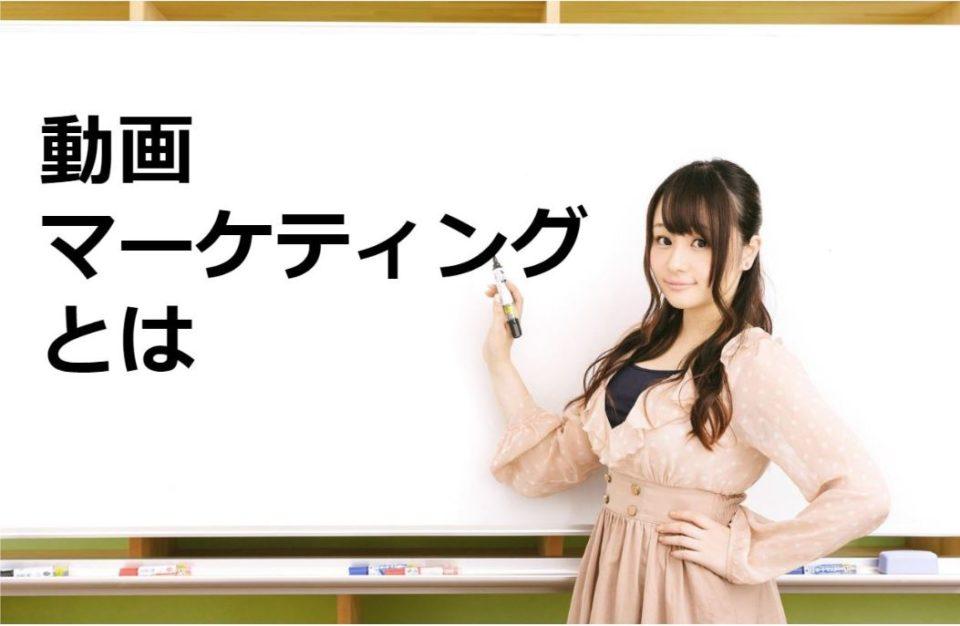 「動画マーケティングとは」と書かれた白板の前で立つ女性