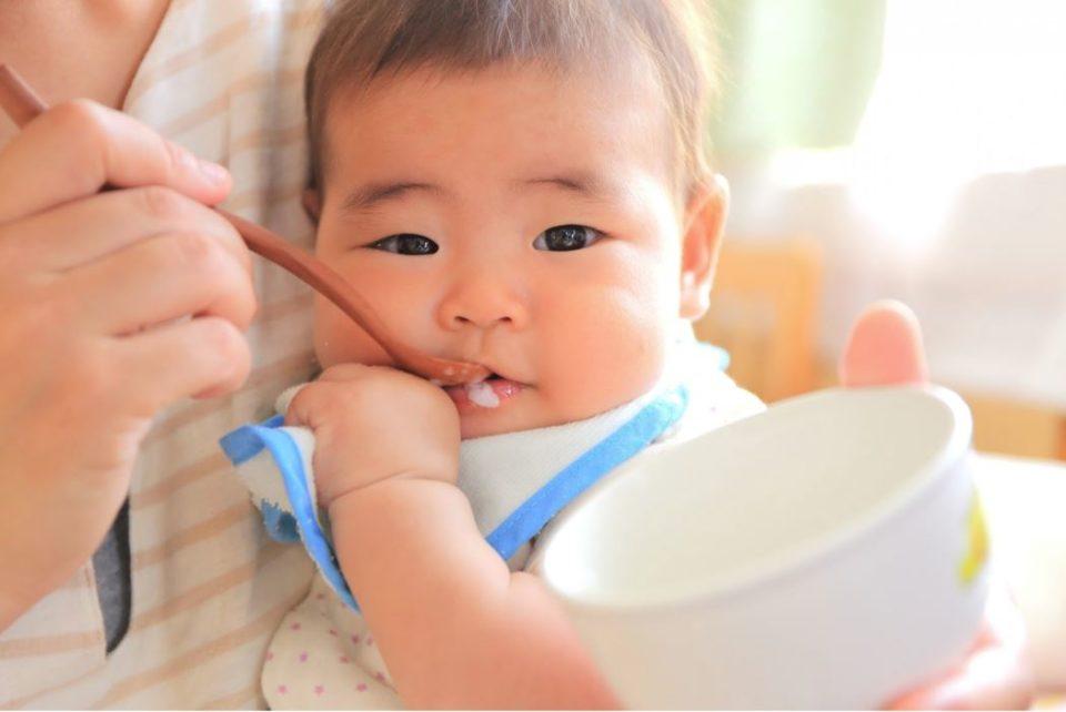 匙でご飯をたべさせられている赤ちゃん