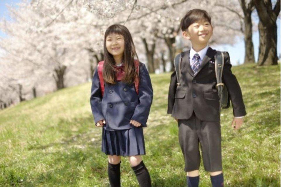 桜並木と、ランドセルを背負った男の子と女の子