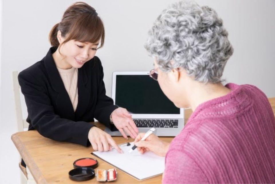 遺言状を書く老女と書き方を指導する女性職員