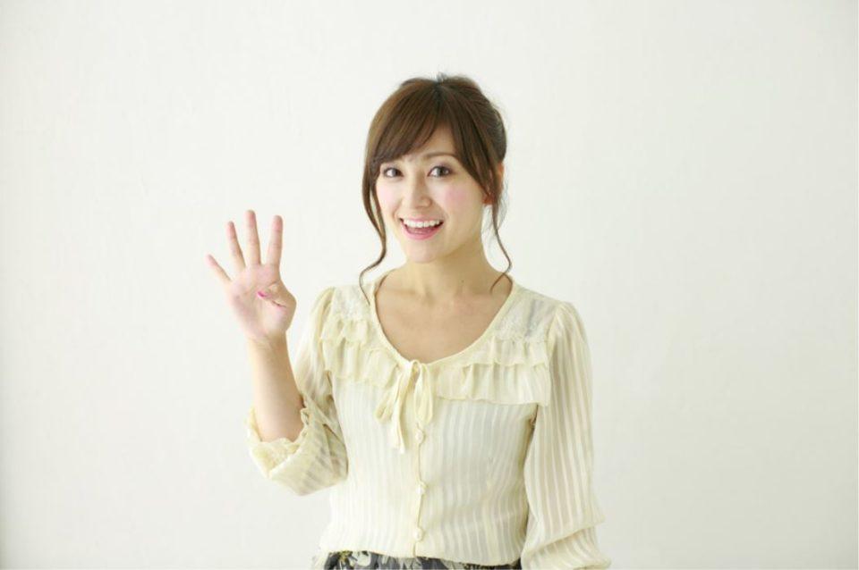 指を4本立てた笑顔の女性