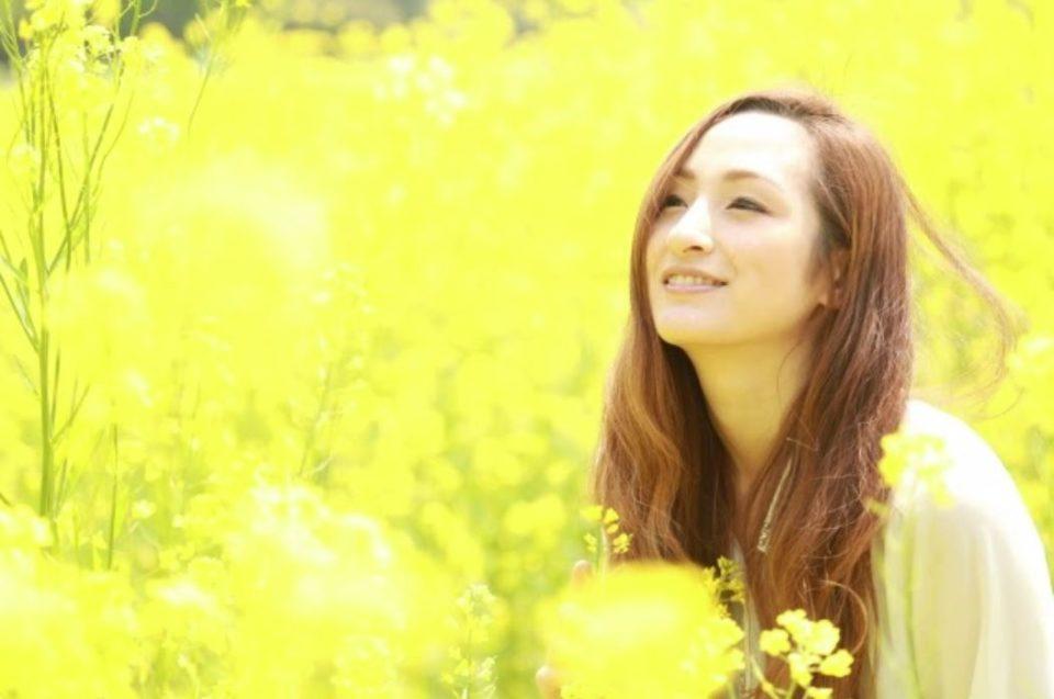 黄色い花畑の中で笑顔のモデル女性