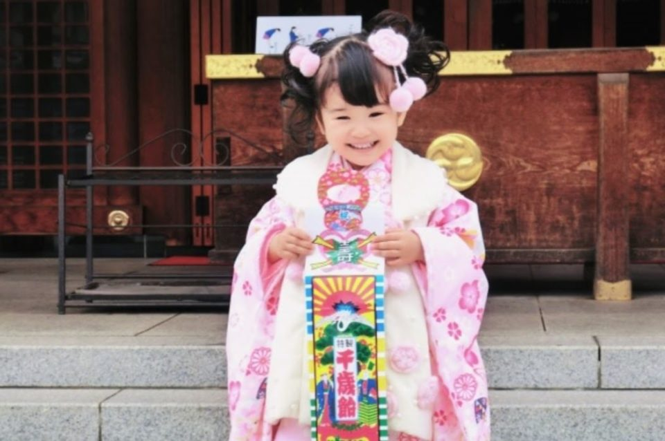 七五三で千歳飴を持って撮影する笑顔の女の子