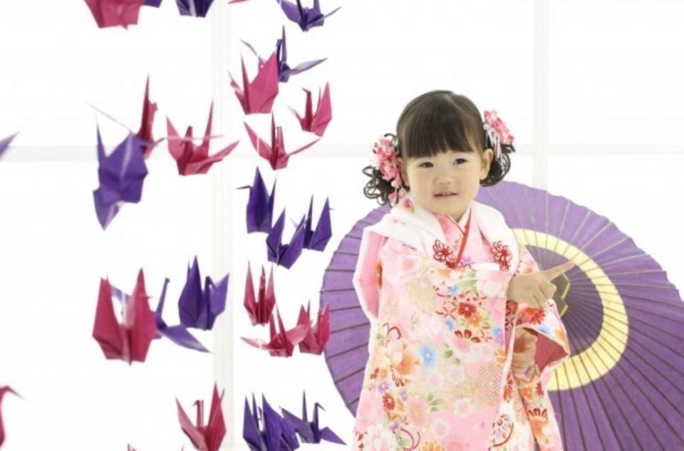 七五三の後撮りをする女の子と折り鶴